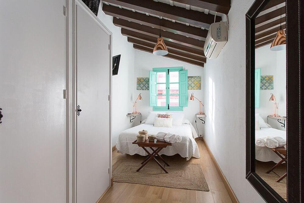 Hình ảnh phòng ngủ nhỏ với cửa sổ đầu giường màu xanh ngọc lam, bộ đội đèn ngủ màu vàng đồng, kệ gỗ cuối giường, thảm trải cói