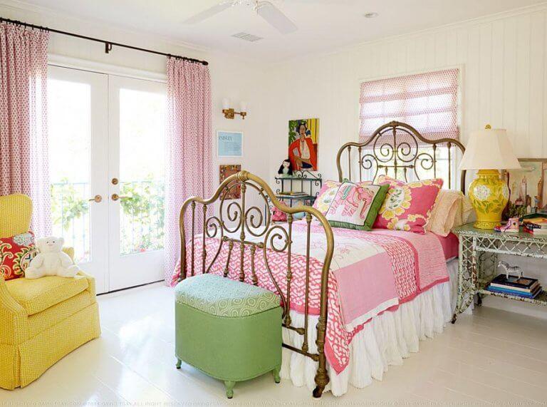 Phòng ngủ nhỏ với ga gối màu hồng, đôn ngồi xanh lá, ghế tựa vàng chanh, rèm cửa họa tiết hồng