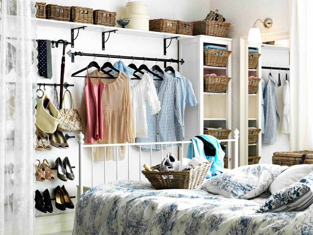 Hình ảnh một góc phòng ngủ với tủ quần áo kiểu mở độc đáo gồm nhiều giỏ đựng bằng mây tre đan, kệ treo kim loại