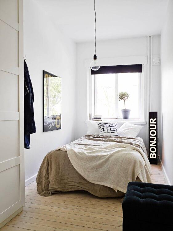 Hình ảnh phòng ngủ nhỏ phong cách tối giản với ga gối màu trắng chủ đạo, tranh treo tường, cửa sổ đầu giường