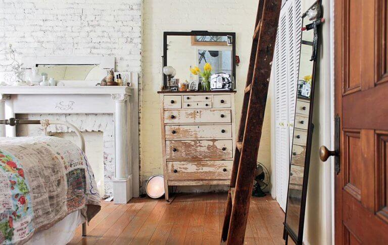 Hình ảnh phòng ngủ nhỏ phong cách mộc mạc với tường gạch thô sơn trắng, tủ cũ, thang lưu trữ, ga gối êm ái
