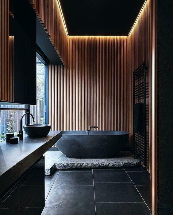 Hình ảnh toàn cảnh phòng tắm phong cách mở tông màu đen chủ đạo với tường ốp gỗ thanh dọc màu sáng, chậu rửa và bồn tắm đá tạo điểm nhấn