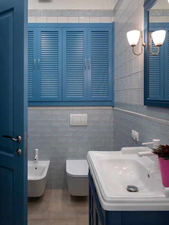 hình ảnh phòng tắm nhỏ mang hơi hướng cổ điển với cửa vào, cửa sổ, tủ đồ màu xanh