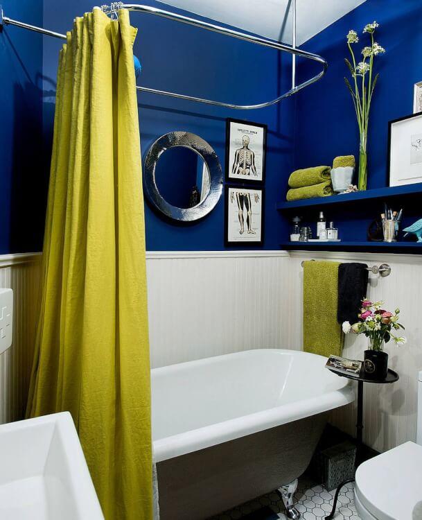 hình ảnh phòng tắm nhỏ với mảng tường sơn xanh đậm, bồn tắm màu trắng, rèm cửa và khăn màu vàng nổi bật