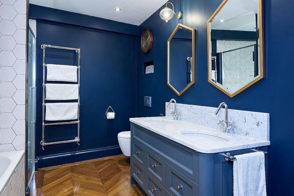 phòng tắm nhỏ với tường sơn xanh đậm, ốp gạch trắng, khung gương lục giác mạ đồng, thang lưu trữ gắn tường