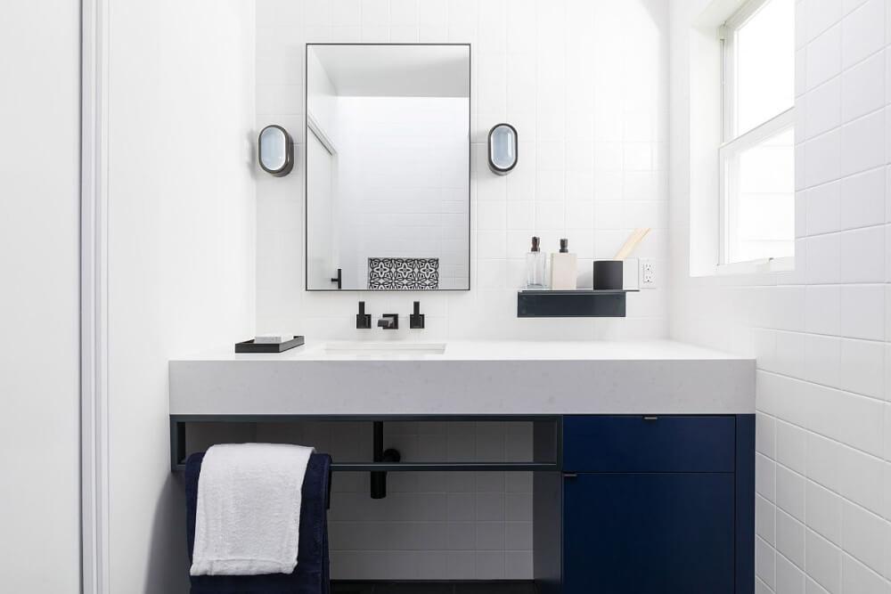hình ảnh phòng tắm nhỏ màu xanh trắng, điểm nhấn màu đen ở khung gương