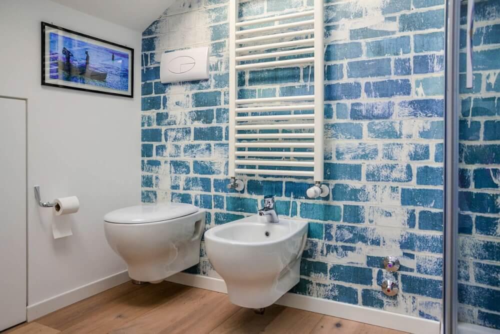 Hình ảnh phòng tắm phong cách Shabby Chic với tường gạch sơn xanh, trang trang trí, thanh treo dạng thang