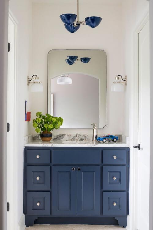 Hình ảnh phòng tắm nhỏ màu trắng chủ đạo, tủ đồ dưới bồn rửa màu xanh nổi bật