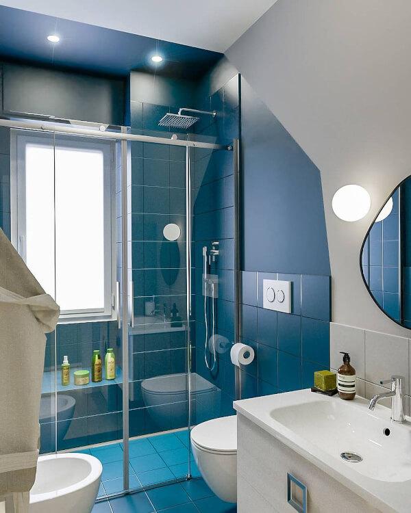 Hình ảnh phòng tắm nhỏ với buồng tắm đứng ốp gạch màu xanh, vách kính, bên ngoài là khu vực vệ sinh, đèn LED âm trần