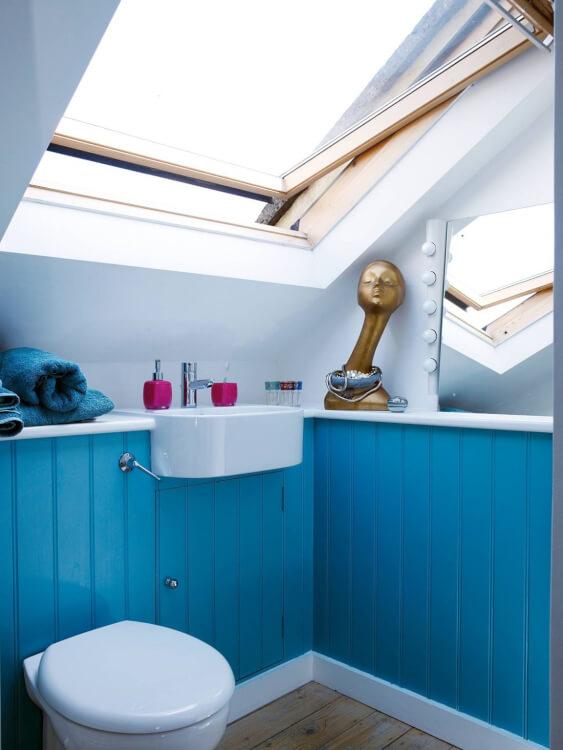 Hình ảnh phòng tắm gác mái với mảng tường sơn xanh da trời, cửa sổ mái