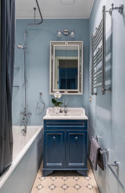 hình ảnh phòng tắm nhỏ với tường và rèm màu xanh nhạt, gạch lát họa tiết hình học