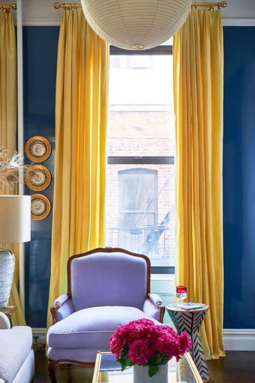 Hình ảnh một góc phòng khách nổi bật với ghế bành màu tím, rèm cửa vàng