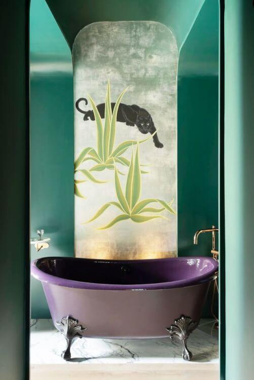 Hình ảnh phòng tắm ấn tượng với tường xanh lá đậm, tranh báo đen, bồn tắm màu tím