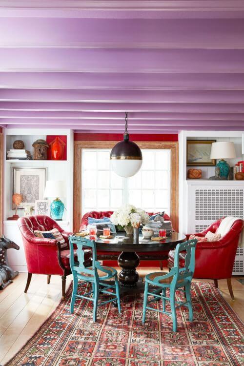 Phòng ăn được bài trí độc đáo với những chiếc ghế màu xanh ngọc lam, trần nhà màu tím, thảm trải thổ cẩm, ghế bành màu đỏ