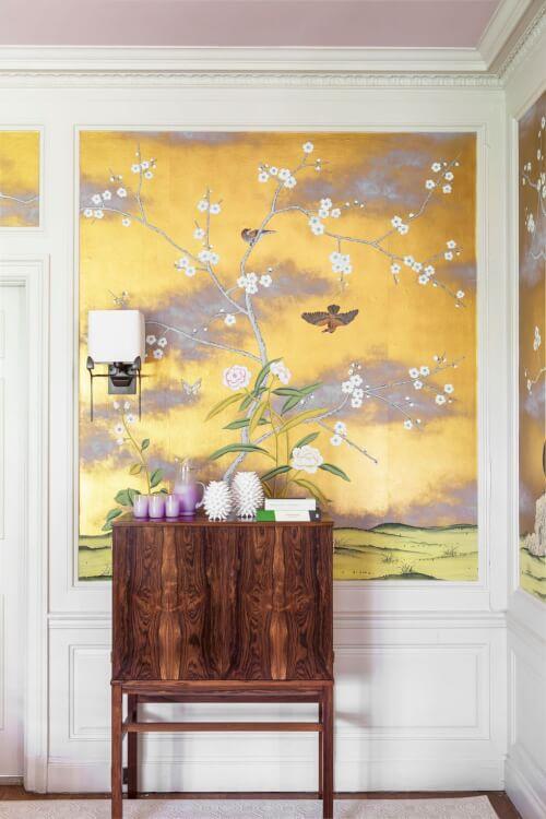 Hình ảnh hành lang nhà với tủ gỗ ấm áp, tranh tường màu vàng tím họa tiết chim hoa mùa xuân