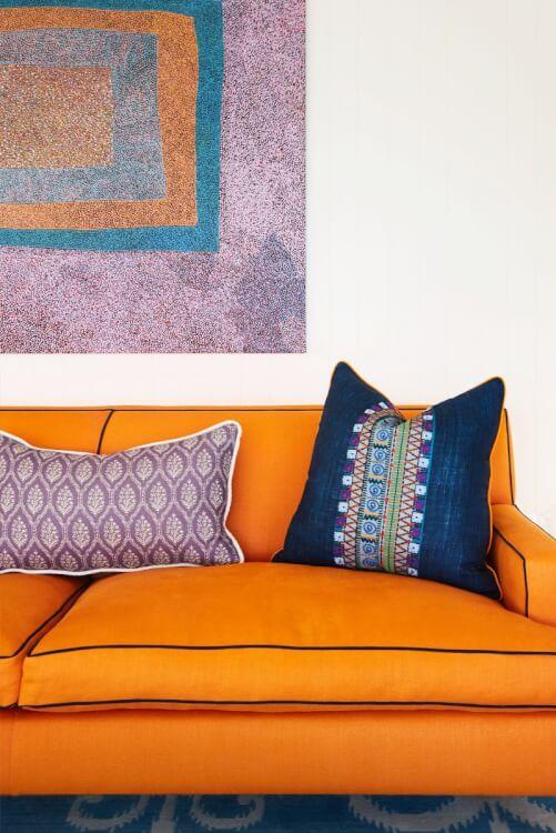 Một góc phòng khách với sofa màu cam, gối tựa tím oải hương cùng tông với tranh tường