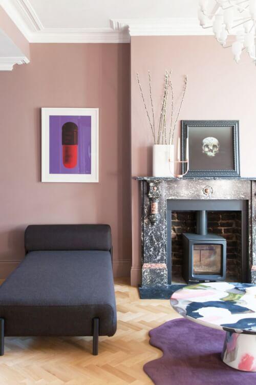 Hình ảnh một góc phòng khách với tường màu hồng tro, sofa xanh than, thảm trải màu tím mộng mơ