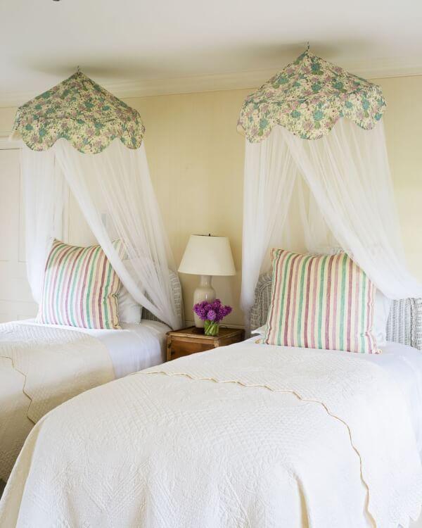Hình ảnh một góc phòng ngủ với giường đôi màu trắng, màn chụp họa tiết hoa văn nhẹ nhàng