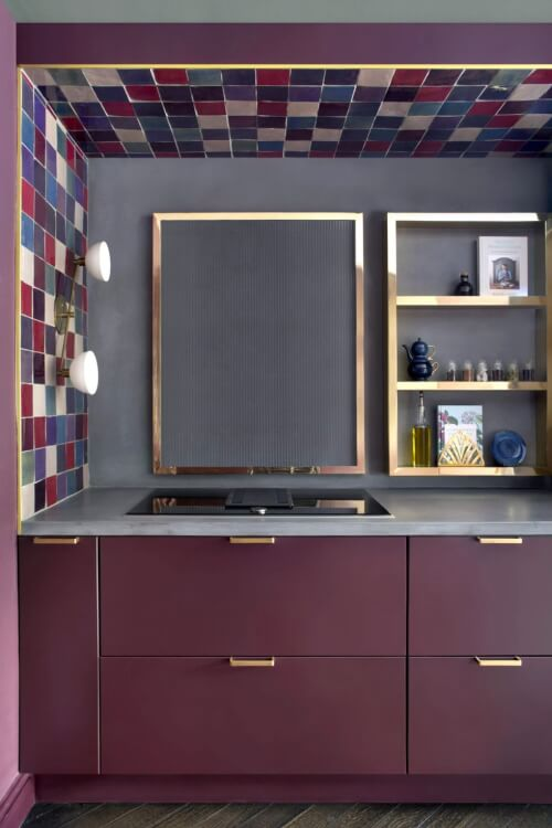 Hình ảnh một góc phòng bếp với tủ màu tím, kệ kim loại, sơn tường than chì và trần ốp gạch màu sắc