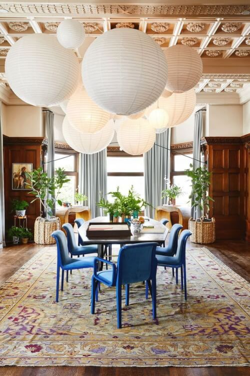 Hình ảnh phòng ăn ấn tượng với ghế màu xanh đậm đặt trên thảm họa tiết tím, đèn thả bằng giấy nhiều cỡ