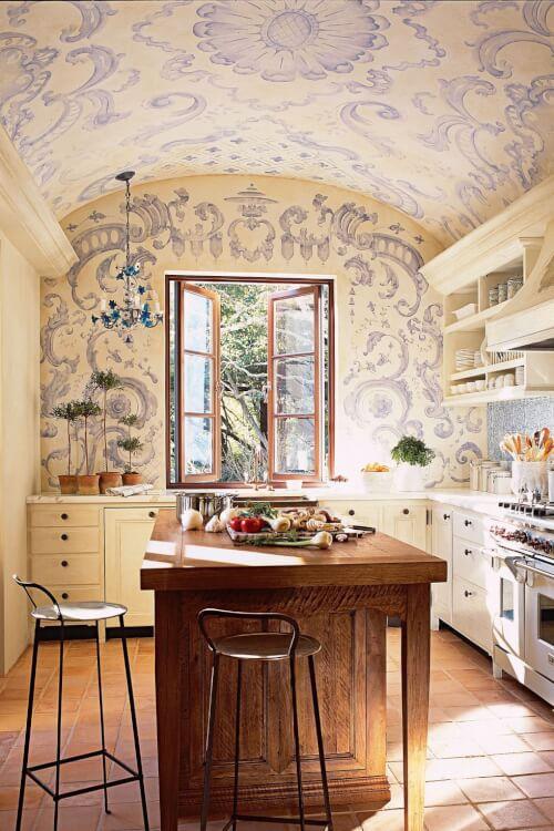 Hình ảnh một góc phòng bếp với bàn đảo bằng gỗ, giấy dán tường họa tiết tím, tủ ngăn kéo màu trắng