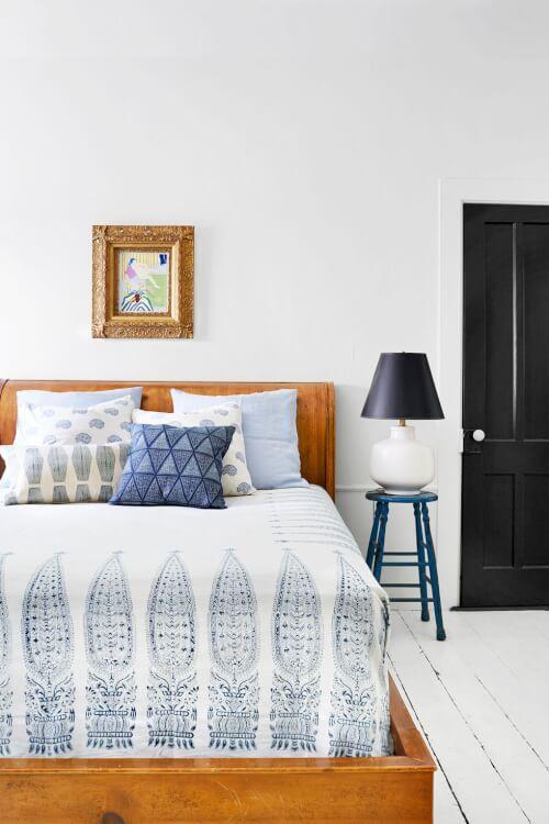 Hình ảnh một góc phòng ngủ với ga gối màu trắng họa tiết xanh dương, cạnh đó là bàn đặt đèn ngủ
