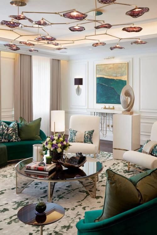 Hình ảnh phòng khách màu xanh lá hài hòa, điểm nhấn là bộ đèn chùm độc đáo