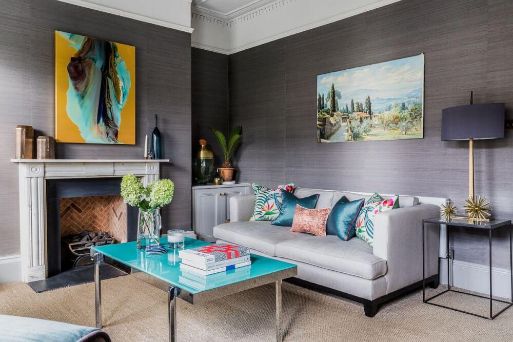 Hình ảnh minh họa cho việc trang trí phòng khách mùa hè với sofa xám, gối tựa xanh lam, tranh treo tường trừu tượng