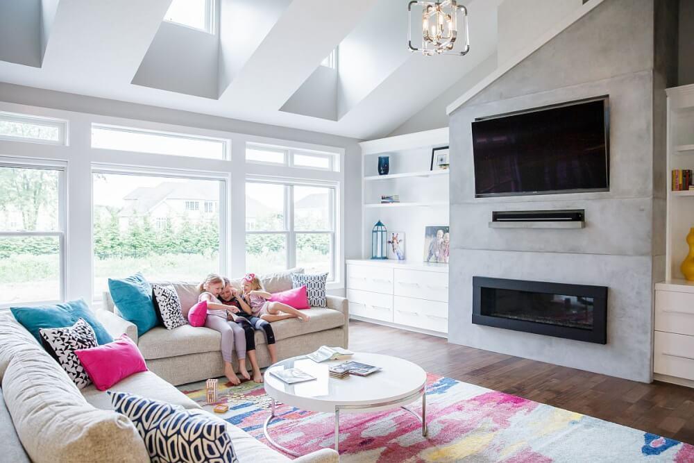 Hình ảnh toàn cảnh Phòng khách màu trung tính sinh động hơn nhờ gối tựa màu sắc, các bé đang ngồi trên sofa