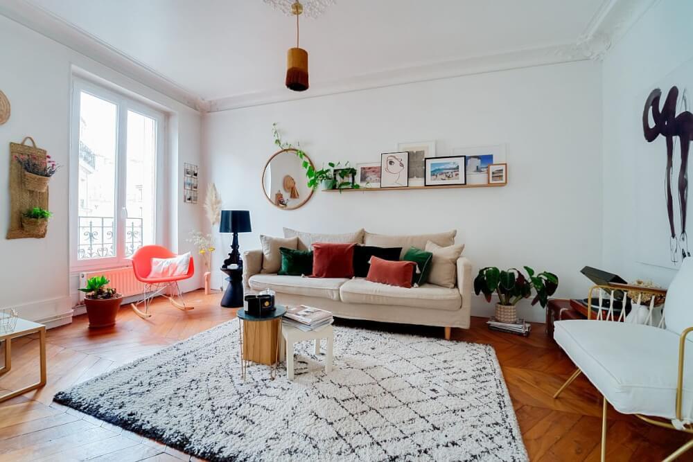 Hình ảnh phòng khách phong cách Shabby-chic sang trọng với gối tựa nhung xanh, hồng vỏ đỗ nổi bật trên sofa trắng
