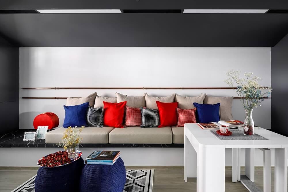 Trang trí phòng khách màu xám - trắng chủ đạo với gối tựa nhiều màu đỏ, xanh, cam