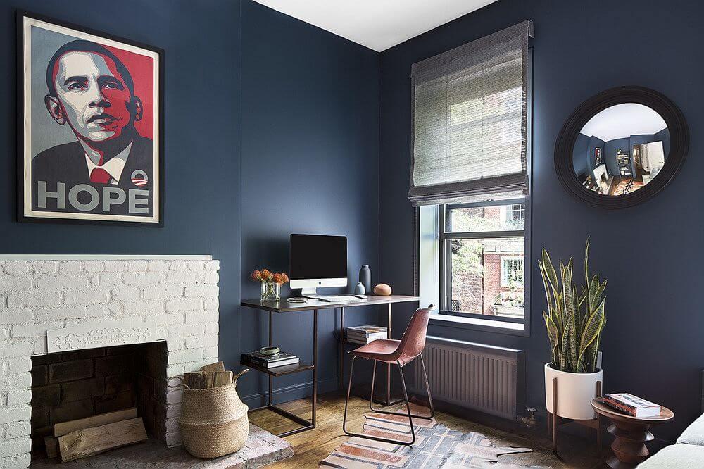 Hình ảnh một góc phòng khách với lò sưởi ốp gạch sơn trắng, tranh Obama treo tường, cạnh cửa sổ kính là bàn làm việc