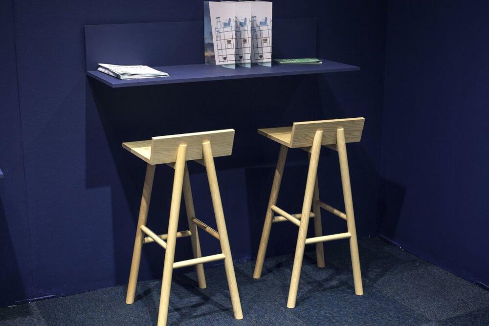 Cận cảnh góc làm viêc với bàn nhỏ gắn tường sơn xanh than, ghế bar bằng gỗ màu trắng