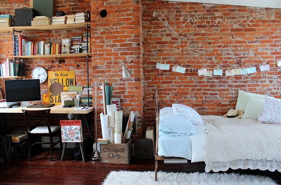 Cận cảnh bức tường gạch đỏ trong phòng ngủ, nơi đặt giường nệm êm ái và góc làm viêc phong cách công nghiệp