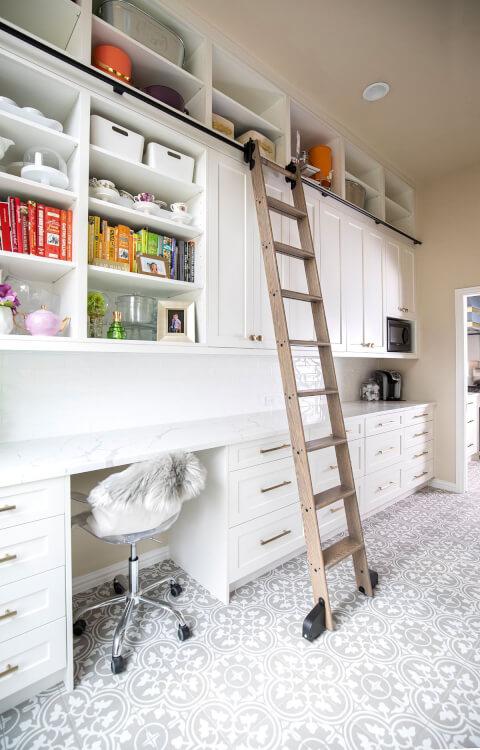 Hình ảnh góc làm việc trong phòng bếp với bàn bếp màu trắng, tủ ngăn kéo nhiều ngăn, cạnh đó là thang gỗ