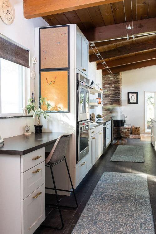 Góc làm việc gọn xinh cạnh cửa sổ phòng bếp với chậu cây xanh nhỏ, tranh treo tường