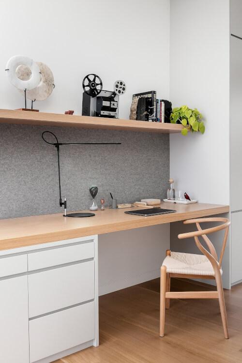 Cận cảnh góc làm việc tại nhà với bàn gỗ dài gắn tường, tủ ngăn kéo
