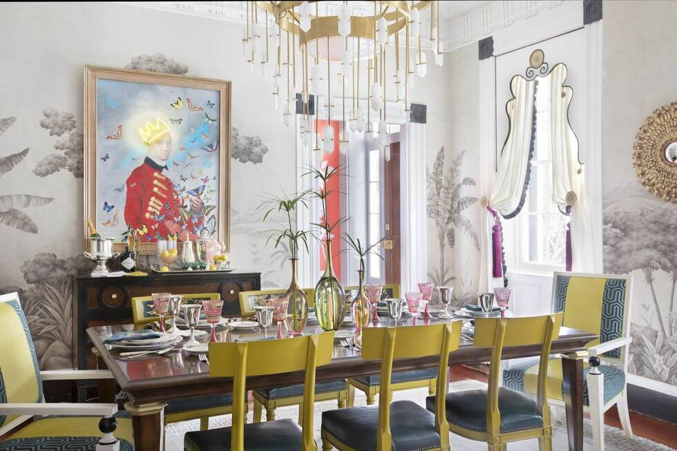 Hình ảnh phòng ăn phong cách cổ điển sang trọng với bàn mặt kính, ghế ngồi màu vàng mù tạ, tranh chân dung treo tường, đèn chùm cổ điển