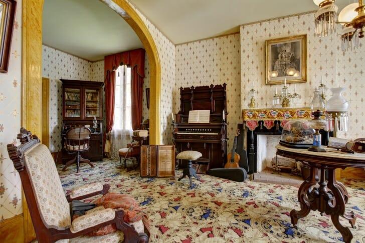 hình ảnh một căn phòng phong cách cổ điển nặng nề với cửa vòm cao rộng, rèm nhung, giấy dán tường, thảm trải hoa văn cầu kỳ, đèn chùm