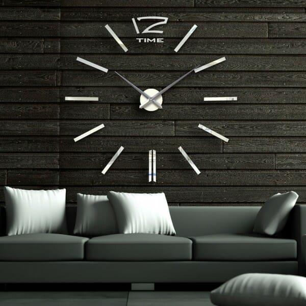 Hình ảnh cận cảnh đồng hồ treo tường khổ lớn nổi bật trên nền xám đen, phía trước là bộ ghế sofa