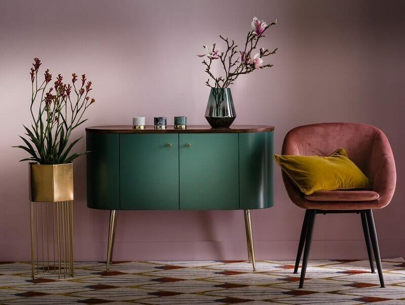 hình ảnh một góc nhà phong cách nội thất Art Deco với tường sơn màu tím nhạt, ghế ngồi màu đỏ đô, tủ màu xanh lá, cây hoa trang trí
