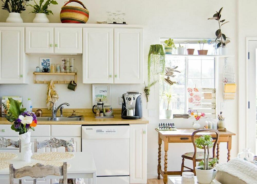 hình ảnh toàn cảnh phòng bếp mùa hè màu trắng với điểm nhấn là những chậu cây xanh tươi