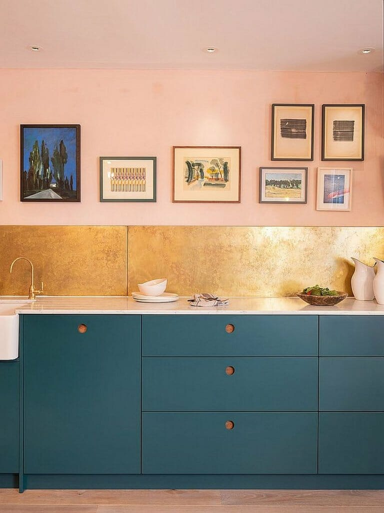 hình ảnh cận cảnh góc bếp đẹp với tường sơn màu hồng, mảng nhỏ ốp gạch vàng đồng, tủ bếp màu xanh dương, tranh treo tường tạo điểm nhấn