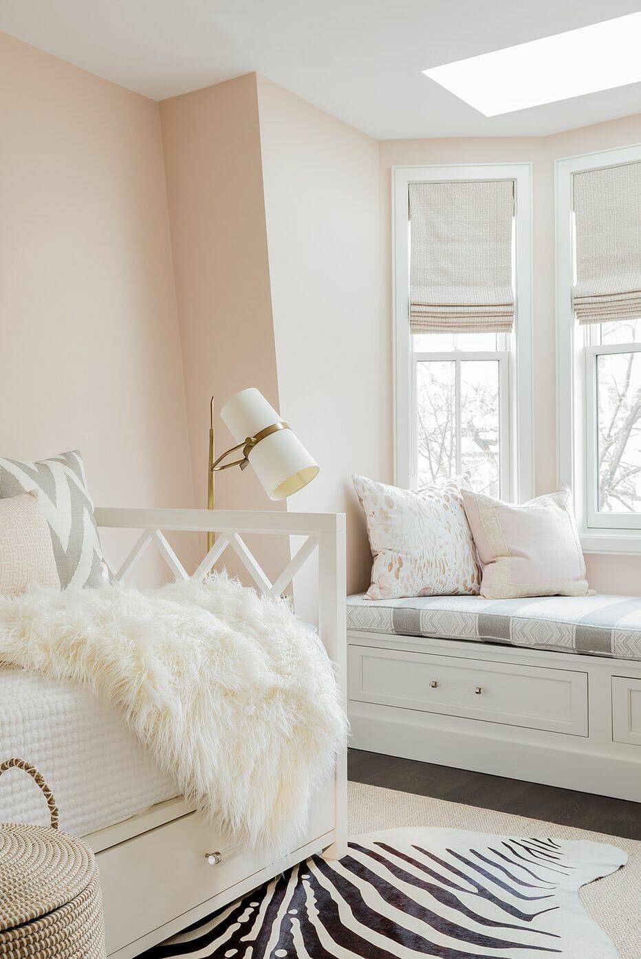 hình ảnh một góc phòng ngủ màu hồng đào có ghế ngồi bên cửa sổ kính