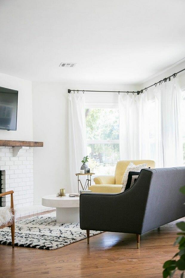 hình ảnh phòng khách màu trắng ngà chủ đạo với điểm nhấn là ghế bành màu xám đen