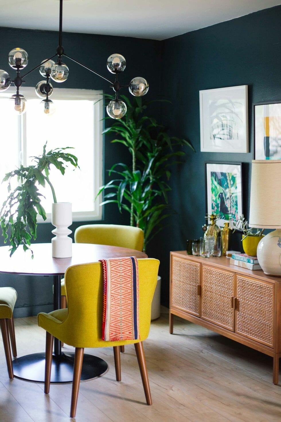 hình ảnh phòng ăn với tường sơn màu xanh mòng két, bàn ăn tròn, ghế vàng, đèn thả thủy tinh, tủ gỗ, tranh treo tường, cây xanh trang trí