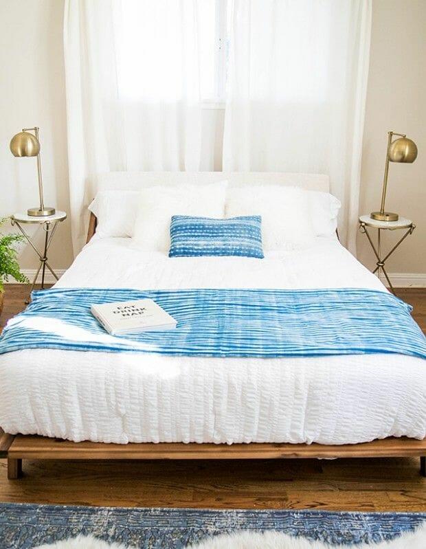 hình ảnh phòng ngủ màu be trắng chủ đạo, điểm nhấn là bộ đèn ngủ màu vàng đông, chăn họa tiết xanh dương