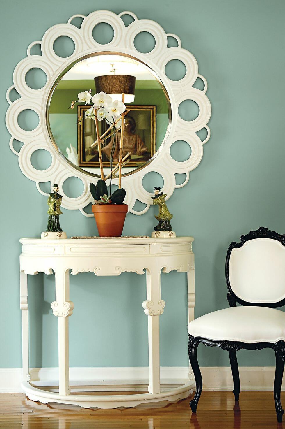 hình ảnh một góc nhà với bàn gương trăng điểm màu trắng, ghế ngồi khung đen, chậu cây trang trí, tượng điêu khắc nhỏ, tường màu xanh lam