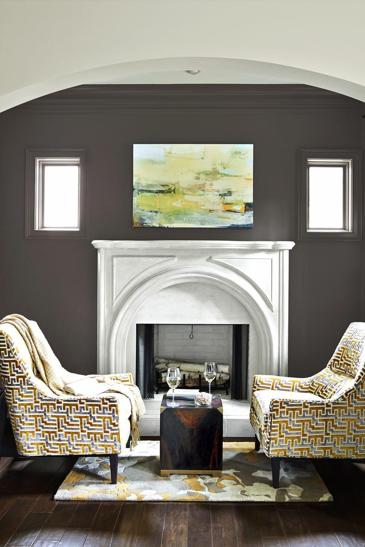 hình ảnh phòng khách nhà nhỏ với sàn và bàn trà màu cà phê, ghế tựa họa tiết bắt mắt, tường sơn màu xám