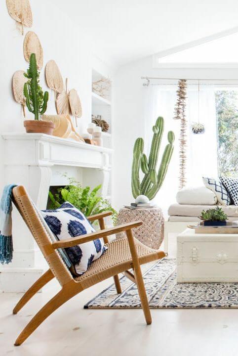 hình ảnh một góc phòng khách màu sáng với ghế ngồi thư giãn, chậu cây xương rồng, quạt nan treo tường